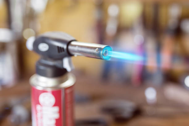 Gas cartridge gun lighter .Close-up nozzle of burner with blue flame jet. Workshop background, scorching of wood Gas cartridge gun lighter .Close-up nozzle of burner with blue flame jet. Workshop background, scorching of wood. flaming torch stock pictures, royalty-free photos & images