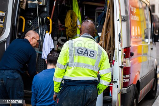 London, UK - 15 February, 2019: color image depicting a crew of male gas engineers sorting through equipment in the back of their van as they attempt to fix a gas leak on a city street in London, UK. The engineer in the foreground wears a high visibility vest with the word 'gas' printed on the back in capital letters. Room for copy space.