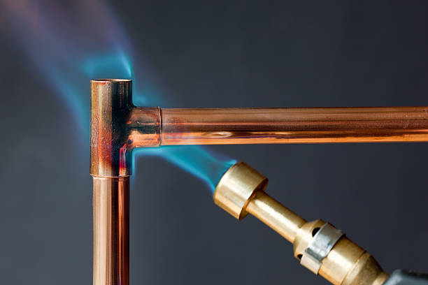 Gas flame heating copper piping before soldering Gas flame heating copper piping before soldering right angle stock pictures, royalty-free photos & images