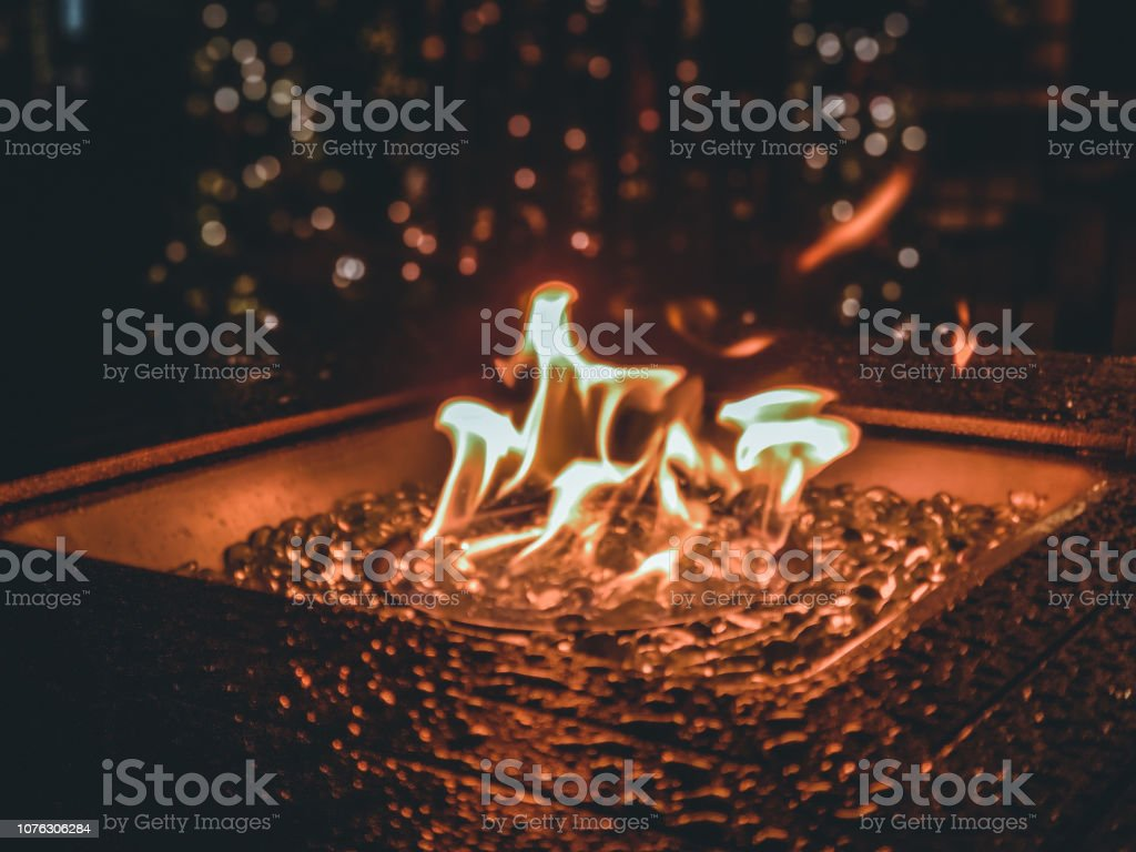 Outdoor fire pit wet from rain with bright gas flames and glass...