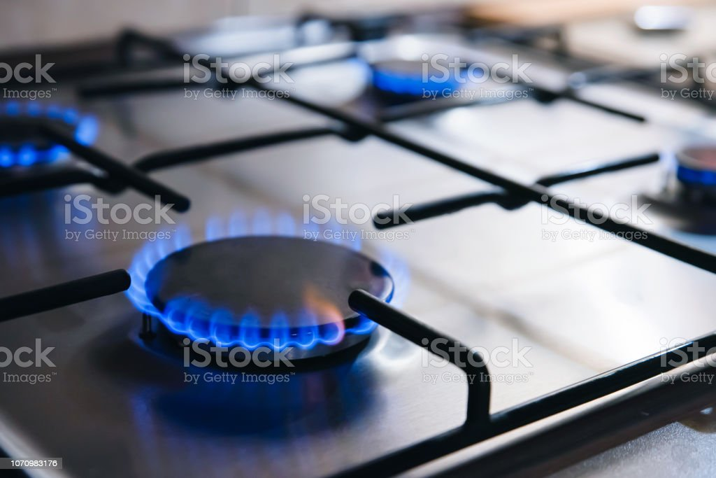Gas kitchen stove cook with blue flames burning Gas kitchen stove cook with blue flames burning. Panel from steel with a gas Appliance Stock Photo