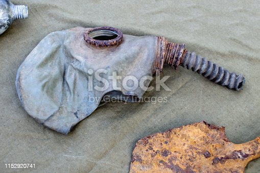 An old gas mask. Rusty old military gas mask and shovel