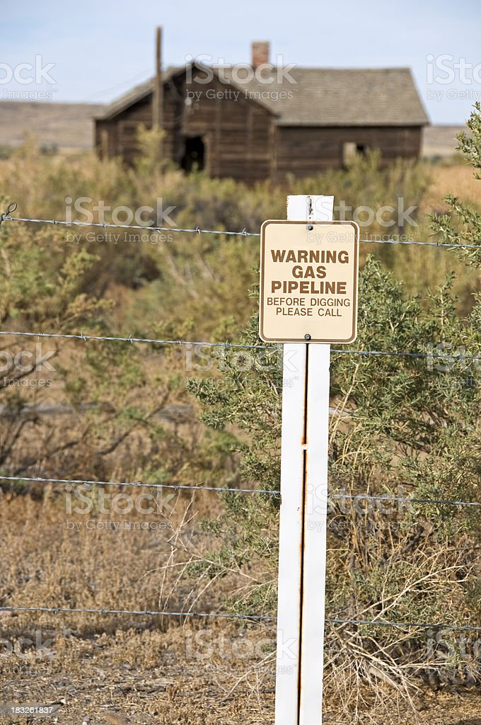 Gas pipeline warning and pioneer's cabin stock photo