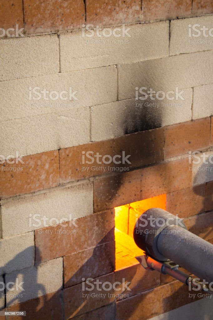 Gas port on the side of a soda kiln with firing in process, oblique view, copy space, soot stock photo