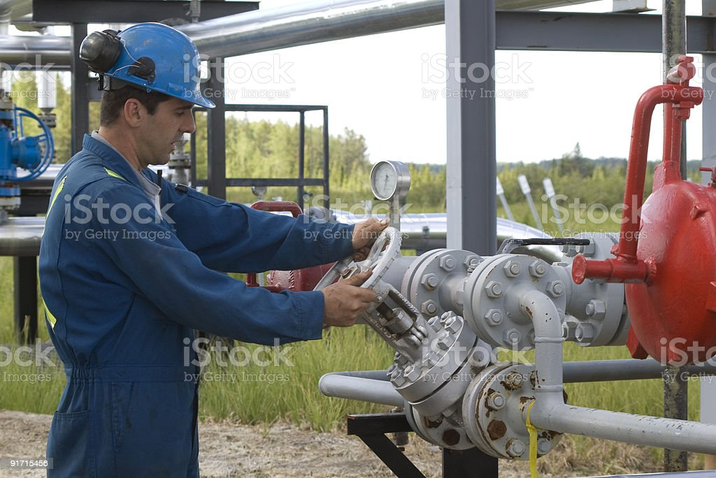 Gas production operator checking gauge outdoors royalty-free stock photo