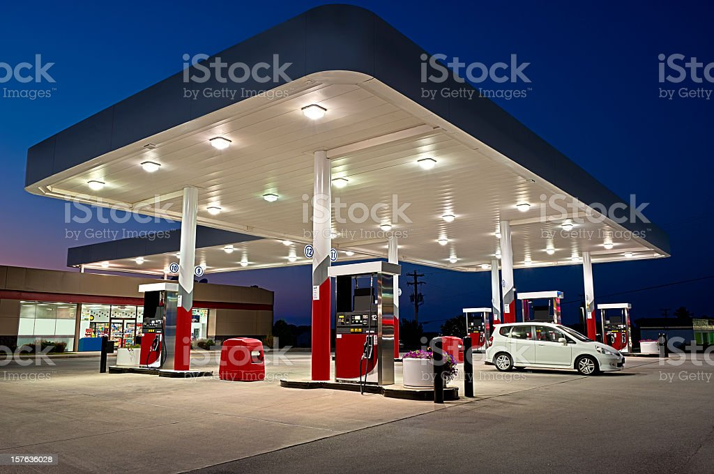 Gas station and convenience store alight at night with 1 car stock photo