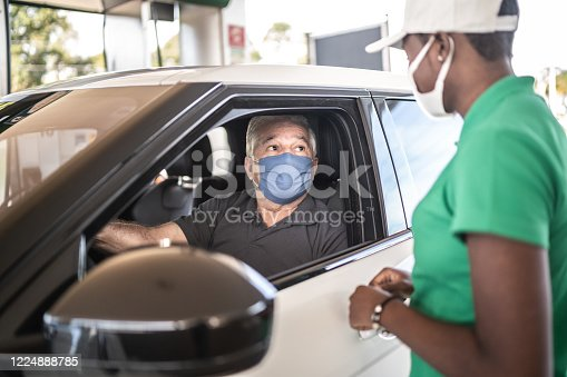Gas station worker talking to customer at car at service station - with face mask