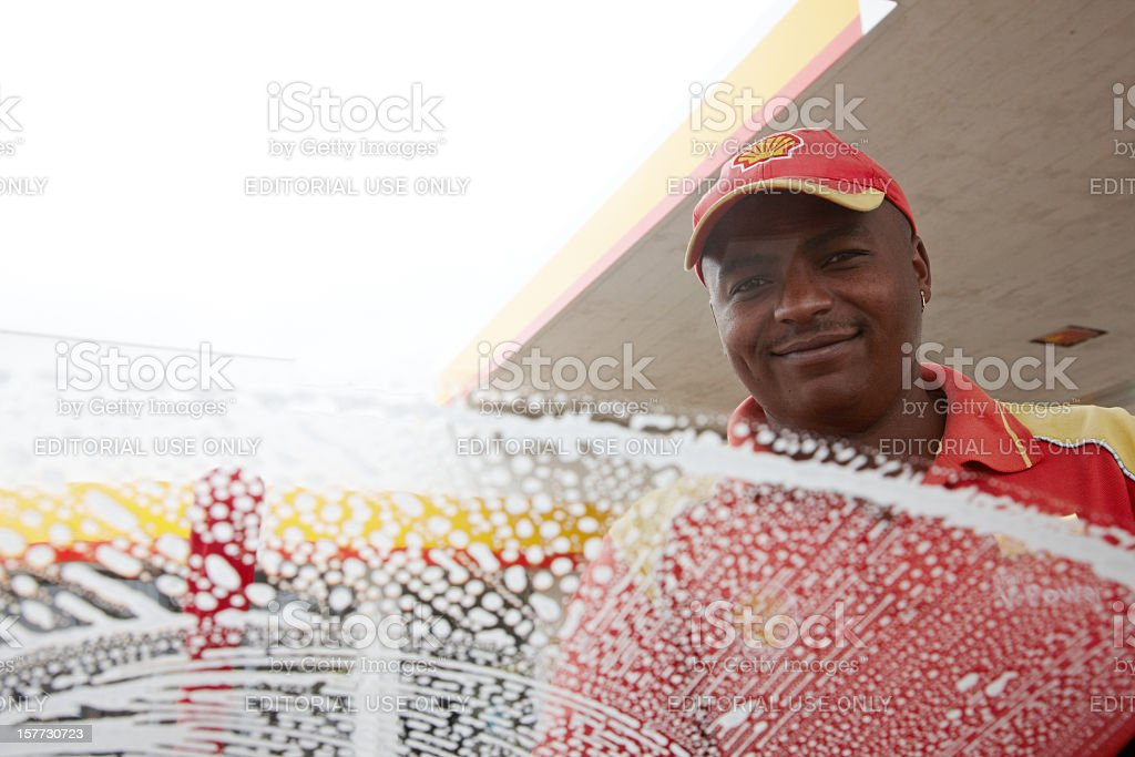 Gas station attendant washing windscreen stock photo