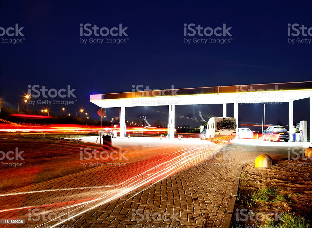 A gas station off of a main highway at night stock photo