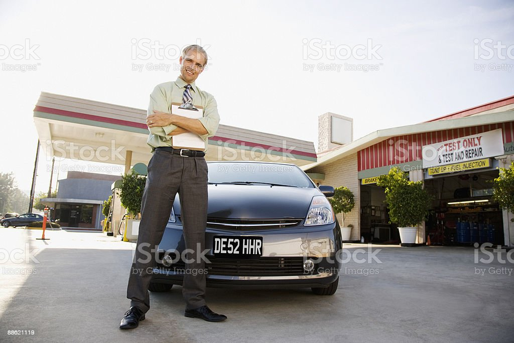 Gas station owner holding clipboard near car royalty-free stock photo