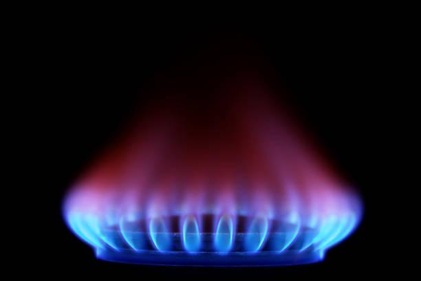 gas stove from side  (blue flames on black) - gas stockfoto's en -beelden