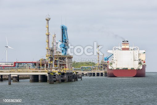 Liquid gas transshipment terminal in harbor Rotterdam, biggest seaport of Europe. In the background a freighter and a wind turbine.
