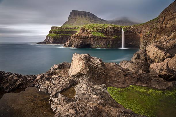 gasadalur village and its waterfall, faroe islands, denmark - faeröer stockfoto's en -beelden