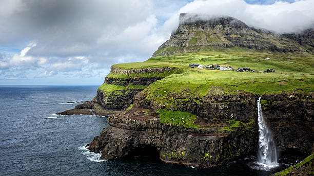 gasadalur  waterfall in vagar, faroe islands - faeröer stockfoto's en -beelden