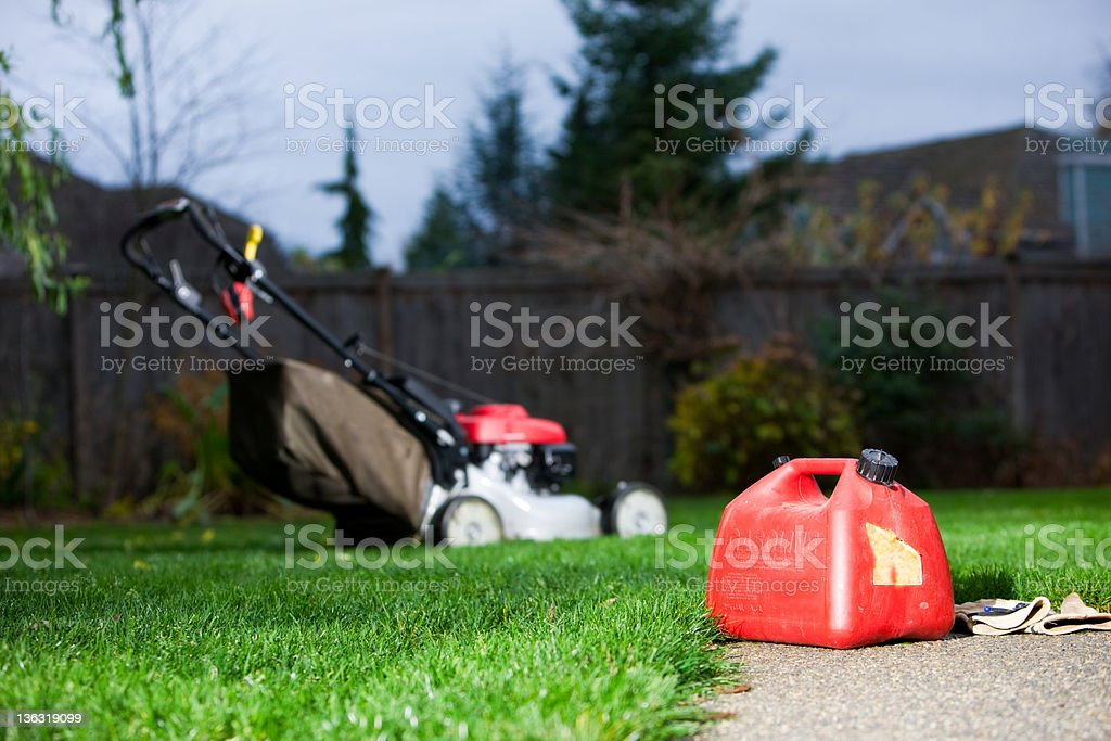Gasoline Can With Mower In Background stock photo