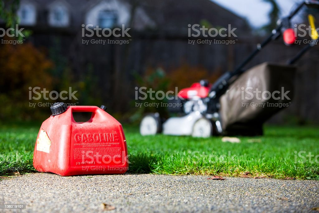 Gasoline container with a mower on the background stock photo