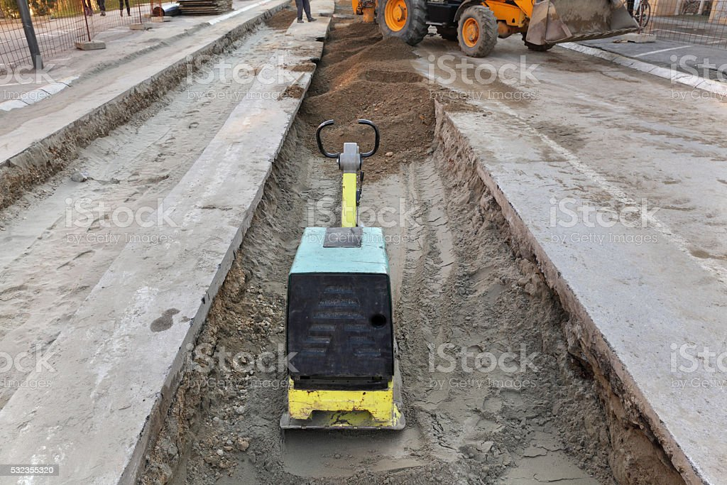 Gasoline or diesel vibratory plate compactor at road construction site stock photo