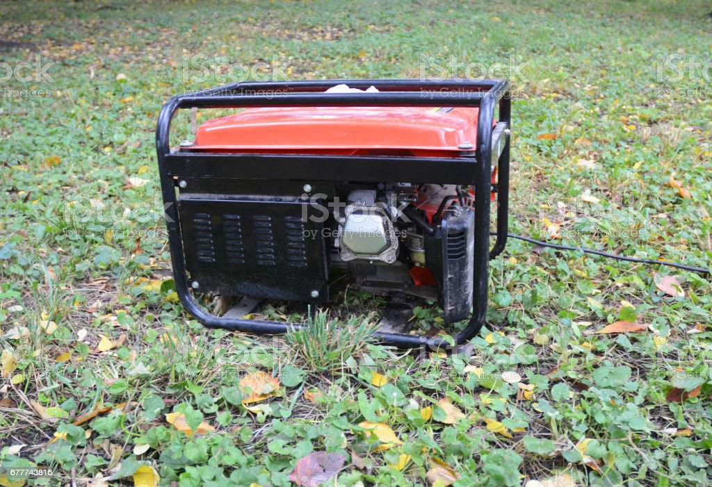 Gasoline Portable Generator. Close up on Mobile Backup Generator in the garden. Standby Generator - Outdoor Power Equipment stock photo