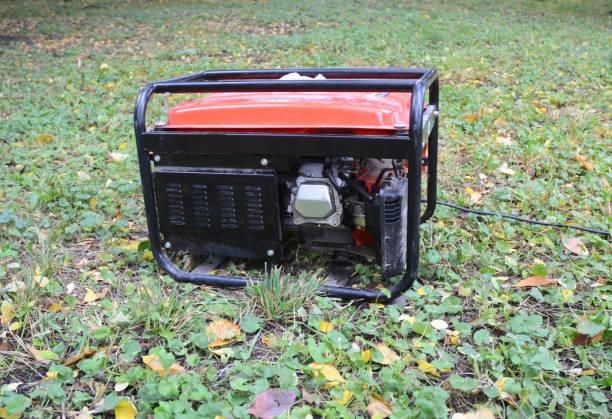 gasoline portable generator. close up on mobile backup generator in the garden. standby generator - outdoor power equipment - generator text stock-fotos und bilder