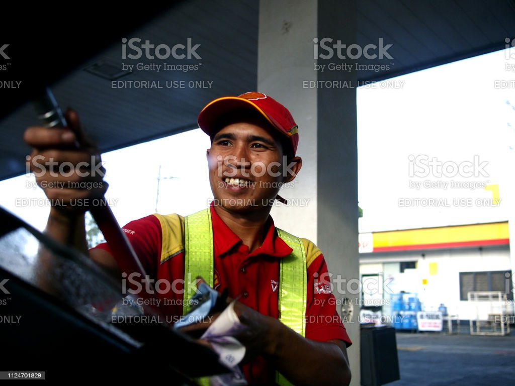 A gasoline station worker cleans the windshield of a customers car while gassing up. stock photo