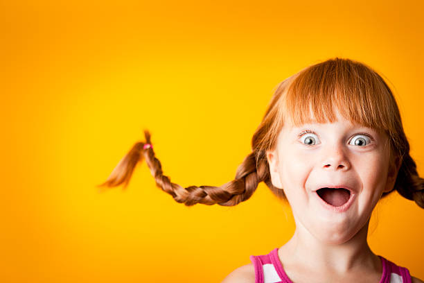 Gasping Red-Haired Girl with Upward Braids and Excited Look stock photo