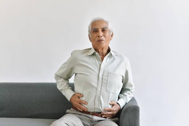 Gastritis Magenschmerzen, Senior alten Mann leiden unter Magenschmerzen, ältere asiatische Menschen halten aufblähenBauchfett. – Foto