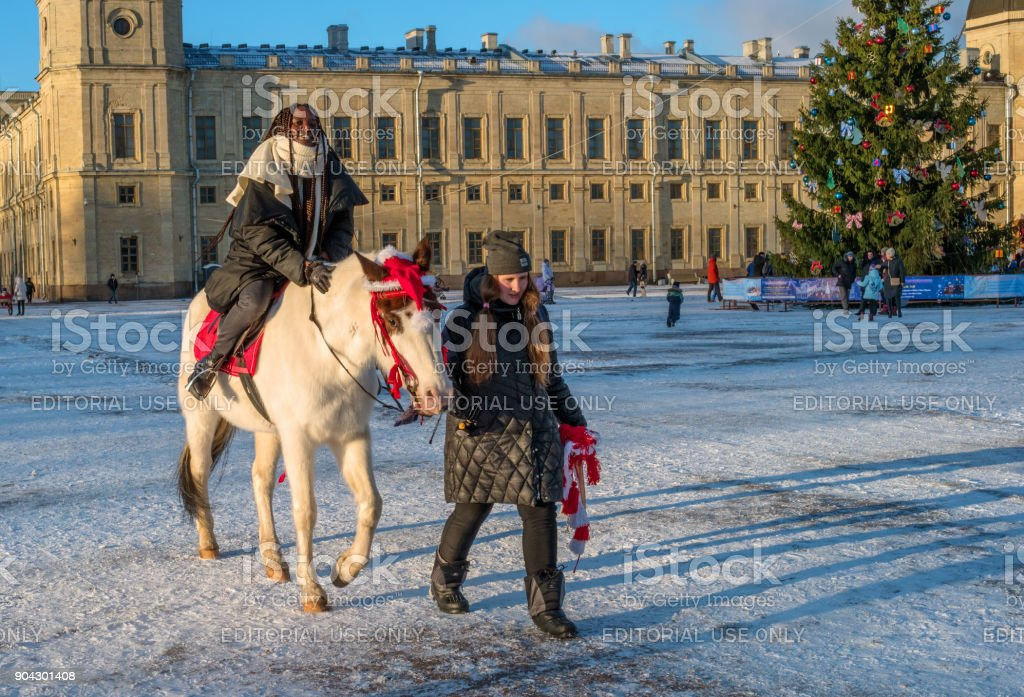 Gatchina Palace, New Year's Fair on the main stage. A festive attraction is riding a horse. stock photo