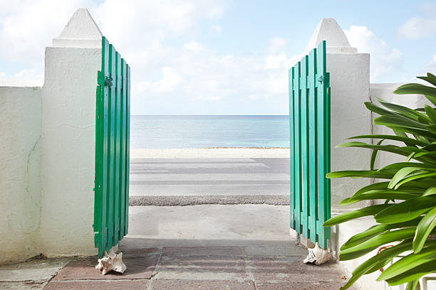 gate looking out onto caribbean sea - open gate stock photos and pictures