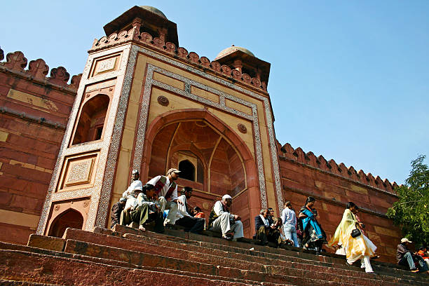 Gate Fatephur Sikri, Uttar Pradesh, India - December 27, 2005: Indians sitting in-front of majestic entrance gate to Jama Masjid. agra jama masjid mosque stock pictures, royalty-free photos & images