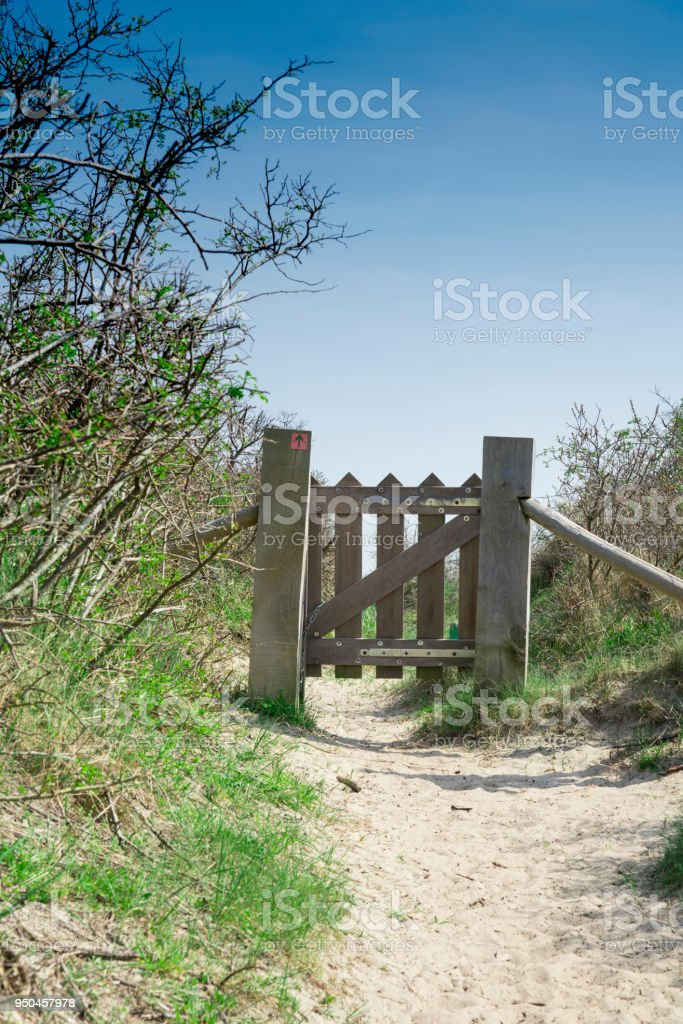 gate to hiking path through the dunes in Burgh Haamstede, The Netherlands stock photo