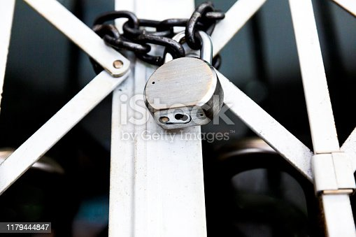 Gate with padlock and chain, dark background with copy space, full frame horizontal composition