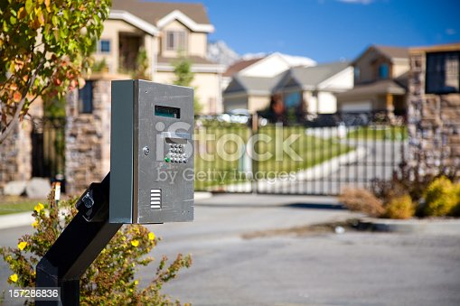 The call box outside the gate of a prestigious gated housing community. The gate and houses can be seen in the out of focus background.
