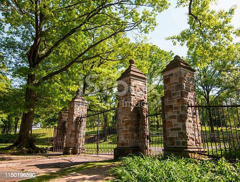 A gated entrance leading into the Homewood Cemetery in Pittsburgh, Pennsylvania, USA on a sunny spring day