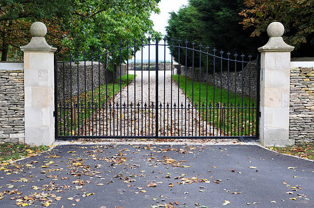 Gates and Driveway of a Country Estate Detail of Ornate Gates and Tree Lined Driveway of an English Country Estate gated community stock pictures, royalty-free photos & images