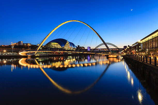 Gateshead Moonlit Evening The image shows the Gateshead Millenium Bridge on a moonlit evening.  In the background are the Sage and the Tyne Bridge. northeastern england stock pictures, royalty-free photos & images