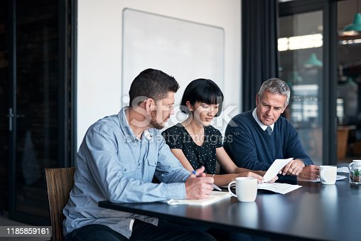 Shot of a group of businesspeople going through paperwork together in an office