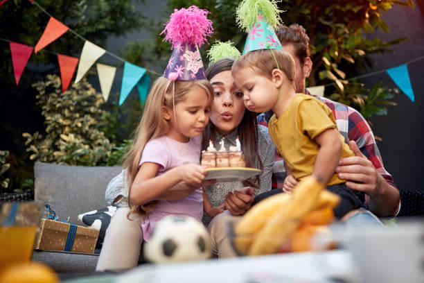 gathered young family blowing birthday candles together. birthday, togetherness concept gathered young family blowing birthday candles together. birthday, togetherness birthday wishes for daughter stock pictures, royalty-free photos & images