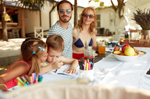 gathered young family of four sitting outdoor at table, spending time together