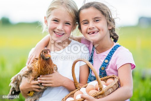 Two elementary age girls are selling eggs at the local farmers. They are holding their chicken and are smiling while looking at the camera.