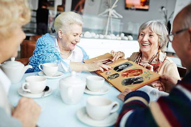 gathering of senior friends - senior fotoboek stockfoto's en -beelden