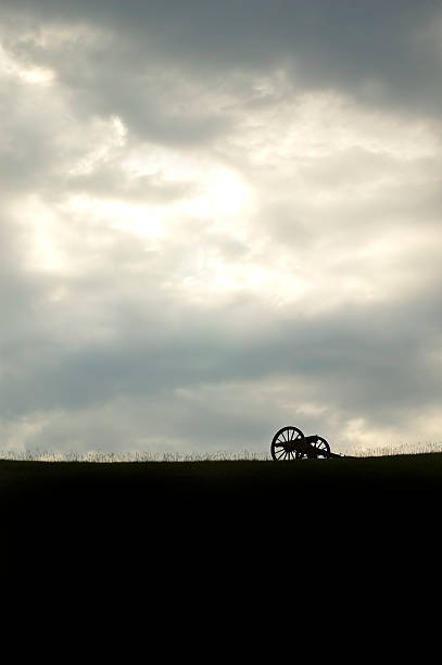 Gathering Storm A single Civile War canon on top of a hill in silhouette civil war memorial minnesota stock pictures, royalty-free photos & images