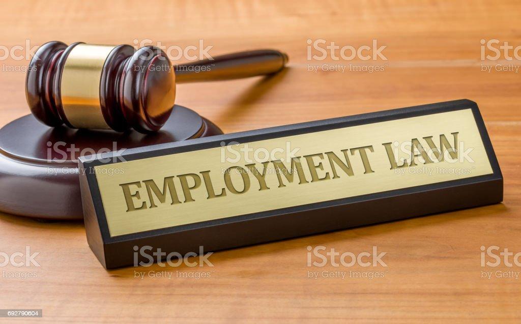 Ein Hammer und ein Namensschild mit Gravur Arbeitsrecht – Foto