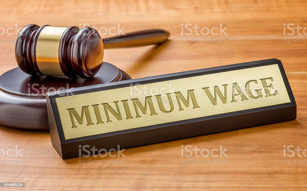 Richterhammer und ein Schild mit dem Namen gravieren Mindestlohn – Foto