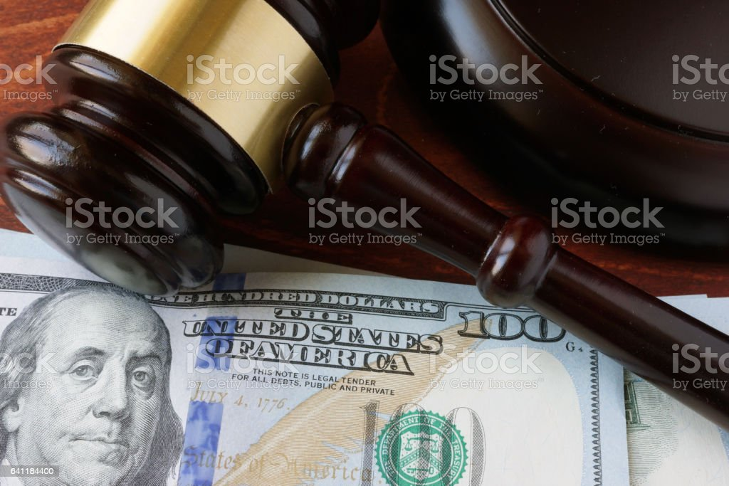 A gavel and currency on a table. stock photo