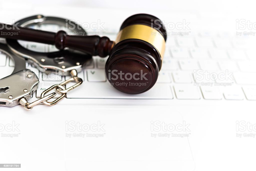 Gavel and handcuffs on laptop keyboard stock photo