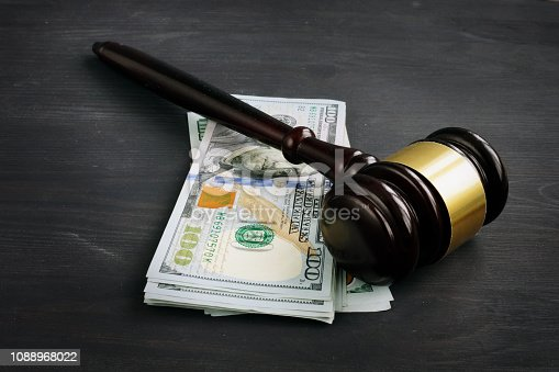 Gavel and money in the court. Penalty or bribe.