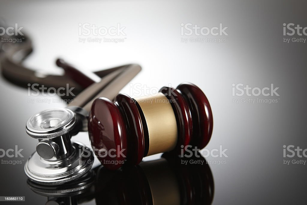 Gavel and stethoscope on a gray background royalty-free stock photo