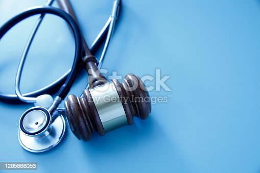 A gavel and a stethoscope on a blue background representing the intersection of the medical and legal industries.