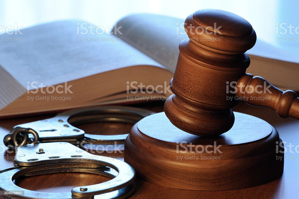 Gavel, book and handcuffs stock photo