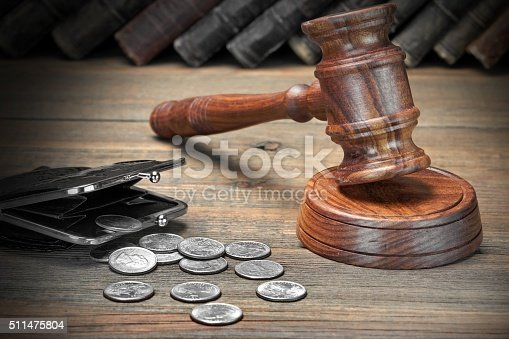 istock Gavel, Empty Purse, Coins, And Old Book On Wooden Table 511475804